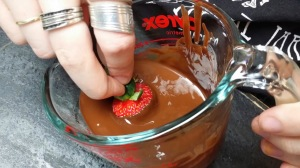 Dipping the strawberries in the melted chocolate.
